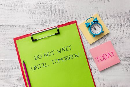 Handwriting text Do Not Wait Until Tomorrow. Conceptual photo needed to do it right away Urgent Better do now Metal clipboard sheets marker alarm clock notes pad wooden background