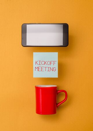 Word writing text Kickoff Meeting. Business photo showcasing Special discussion on the legalities involved in the project Coffee cup colored sticky note electronic device yolk color background
