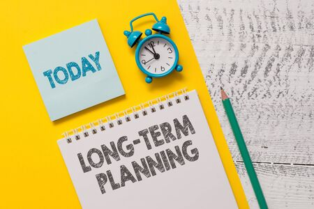 Text sign showing Long Term Planning. Business photo showcasing Establish Expected Goals five or more years ahead Spiral notepad paper sheet marker alarm clock retro wooden background 免版税图像