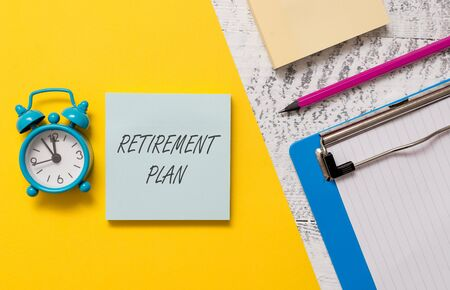 Word writing text Retirement Plan. Business photo showcasing saving money in order to use it when you quit working Notepads clipboard colored paper sheet marker alarm clock wooden background Banque d'images