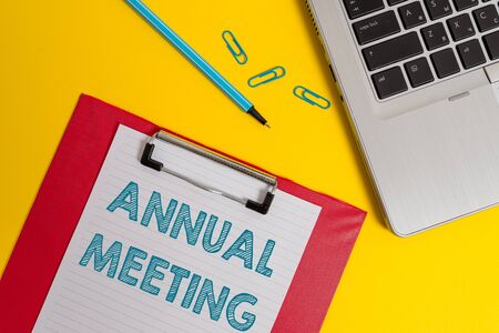 Word writing text Annual Meeting. Business photo showcasing Yearly gathering of an organization interested shareholders Open laptop clipboard blank paper sheet marker clips colored background 免版税图像