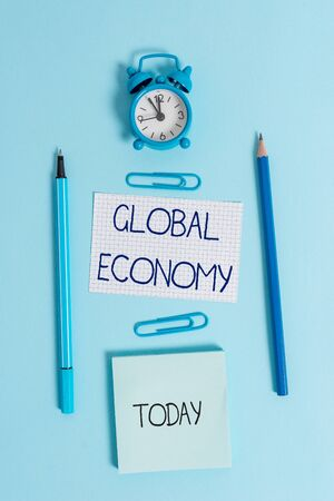 Writing note showing Global Economy. Business concept for System of industry and trade around the world Capitalism Alarm clock squared paper sheet notepad markers colored background