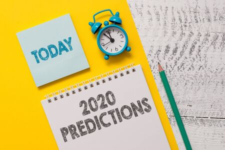 Text sign showing 2020 Predictions. Business photo showcasing list of things you feel that going to happen without proof Spiral notepad paper sheet marker alarm clock retro wooden background