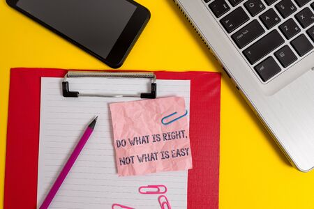 Word writing text Do What Is Right Not What Is Easy. Business photo showcasing willing to stand up for what is right Laptop clipboard sheet clips pencil note smartphone colored background 免版税图像