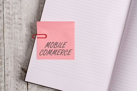 Writing note showing Mobile Commerce. Business concept for Using mobile phone to conduct commercial transactions online Notebook stationary placed above classic wooden backdrop