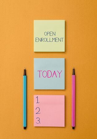 Writing note showing Open Enrollment. Business concept for The yearly period when showing can enroll an insurance Front view colored sticky note two ballpoints cool yolk background 스톡 콘텐츠