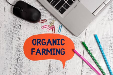 Text sign showing Organic Farming. Business photo showcasing an integrated farming system that strives for sustainability Metallic slim laptop speech bubble colored clips pens mouse wooden vintage