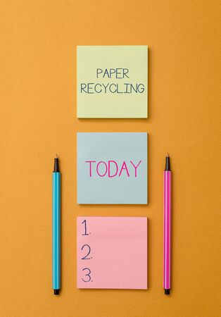 Writing note showing Paper Recycling. Business concept for Using the waste papers in a new way by recycling them Front view colored sticky note two ballpoints cool yolk background