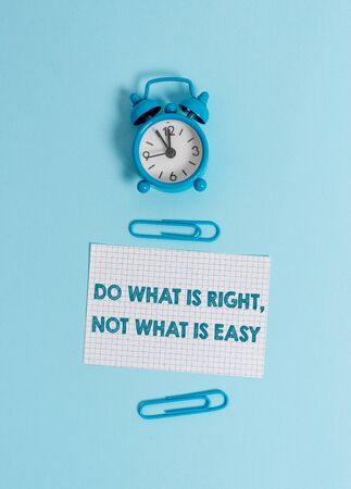 Handwriting text writing Do What Is Right Not What Is Easy. Conceptual photo willing to stand up for what is right Alarm clock wakeup squared blank paper sheet clips colored background