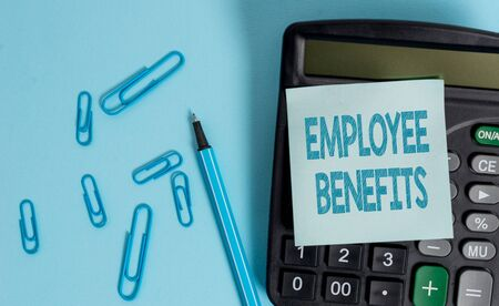 Writing note showing Employee Benefits. Business concept for Indirect and noncash compensation paid to an employee Electronic calculator blank sticky note clips marker colored background