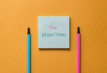 Text sign showing Tax Deductions. Business photo showcasing an amount or cost that subtracted from someone s is income Front view blank colored sticky note two ballpoints cool yolk background Stock fotó
