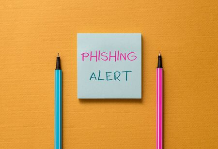 Text sign showing Phishing Alert. Business photo showcasing aware to fraudulent attempt to obtain sensitive information Front view blank colored sticky note two ballpoints cool yolk background