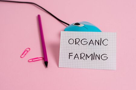 Word writing text Organic Farming. Business photo showcasing an integrated farming system that strives for sustainability Wire vintage mouse clips marker squared paper sheet colored background