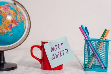 Writing note showing Work Safety. Business concept for policies and procedures in place to ensure health of employees Globe map world earth coffee cup sticky note pens holder wooden table Archivio Fotografico
