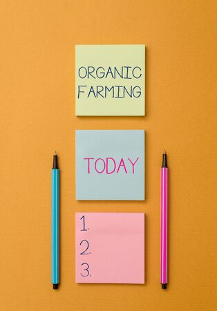 Writing note showing Organic Farming. Business concept for an integrated farming system that strives for sustainability Front view colored sticky note two ballpoints cool yolk background
