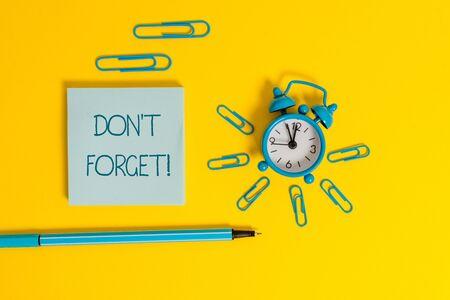 Wort schreiben Text nicht vergessen. Geschäftsfoto, das verwendet wird, um jemanden an eine wichtige Tatsache oder ein Detail zu erinnern Metallwecker-Weckclips Kugelschreiber-Notizblock farbiger Hintergrund