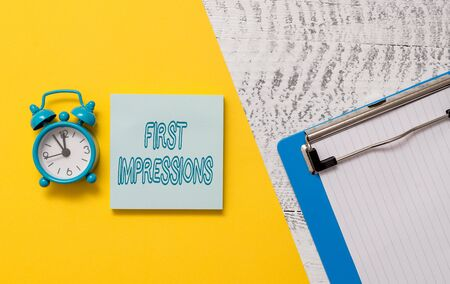 Conceptual hand writing showing First Impressions. Concept meaning What a demonstrating thinks of you when they first meet you Notepad colored paper sheet alarm clock wooden background