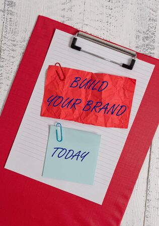 Conceptual hand writing showing Build Your Brand. Concept meaning enhancing brand equity using advertising campaigns Clipboard paper crushed sticky note clip wooden background