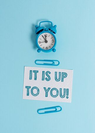 Handwriting text writing It Is Up To You. Conceptual photo Used to tell a demonstrating that they are the one to decide Alarm clock wakeup squared blank paper sheet clips colored background