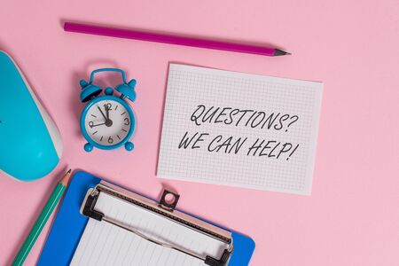 Writing note showing Questions question We Can Help. Business concept for offering help to those who wants to know Alarm clock clipboard paper sheets mouse markers colored background