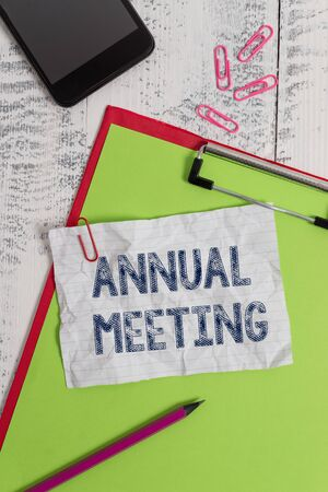 Handwriting text Annual Meeting. Conceptual photo Yearly gathering of an organization interested shareholders Clipboard paper sheet pencil smartphone note clips wooden retro background