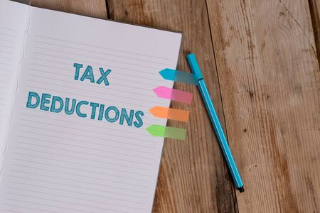 Conceptual hand writing showing Tax Deductions. Concept meaning an amount or cost that subtracted from someone s is income Striped notebook colored arrow banners ballpoint wooden background