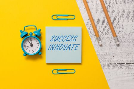 Text sign showing Success Innovate. Business photo text make organizations more adaptive to market forces Notepad clips colored paper sheet markers alarm clock wooden background