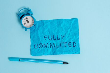 Writing note showing Fully Committed. Business concept for Extremely agreed to do something in life definitely Metal vintage alarm clock crushed sheet marker sky colored background