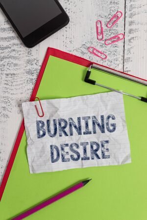 Handwriting text Burning Desire. Conceptual photo Extremely interested in something Wanted it very much Clipboard paper sheet pencil smartphone note clips wooden retro background