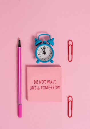 Conceptual hand writing showing Do Not Wait Until Tomorrow. Concept meaning needed to do it right away Urgent Better do now Metal alarm clock blank notepad marker clips colored background Foto de archivo