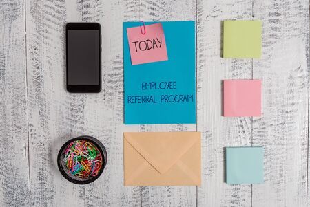 Handwriting text Employee Referral Program. Conceptual photo employees are rewarded for introducing recruits Envelope letter smartphone note clips notepads wooden vintage background
