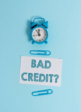 Handwriting text writing Bad Credit . Conceptual photo inability of a demonstrating to repay a debt on time and in full Alarm clock makeup squared blank paper sheet clips colored background