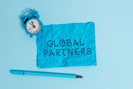 Writing note showing Global Partners. Business concept for Two or more firms from different countries work as a team Metal vintage alarm clock crushed sheet marker sky colored background