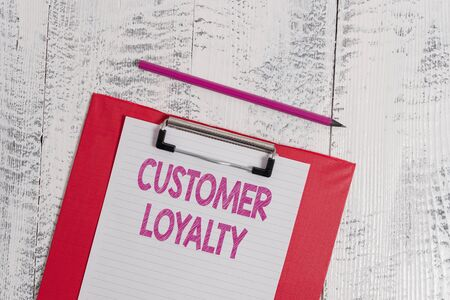Handwriting text Customer Loyalty. Conceptual photo result of consistently positive emotional experience Colored clipboard blank paper sheet pencil old wooden vintage background