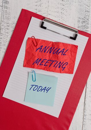 Conceptual hand writing showing Annual Meeting. Concept meaning yearly meeting of the general membership of an organization Clipboard paper crushed sticky note clip wooden background