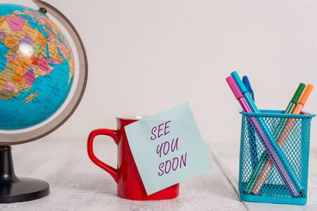 Writing note showing See You Soon. Business concept for used for saying goodbye to someone and going to meet again soon Globe map world earth coffee cup sticky note pens holder wooden table