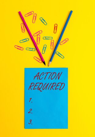 Word writing text Action Required. Business photo showcasing Regard an action from someone by virtue of their position Blank paper sheet message reminder pencils clips colored background