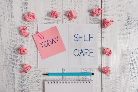 Text sign showing Self Care. Business photo text the practice of taking action to improve one s is own health Squared spiral notepad clip note highlighter paper balls wooden background Stock fotó