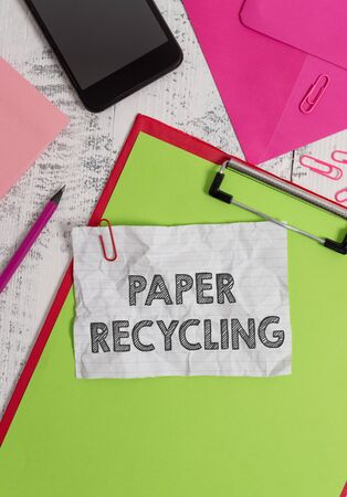 Conceptual hand writing showing Paper Recycling. Concept meaning Using the waste papers in a new way by recycling them Clipboard sheet pencil smartphone clips notepad wooden back