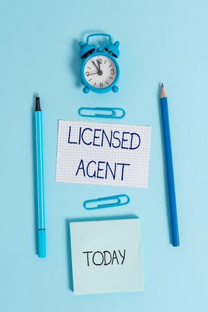 Writing note showing Licensed Agent. Business concept for Authorized and Accredited seller of insurance policies Alarm clock squared paper sheet notepad markers colored background