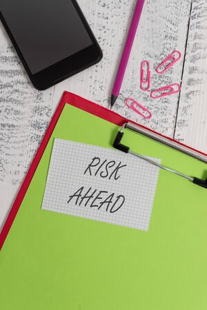 Handwriting text writing Risk Ahead. Conceptual photo A probability or threat of damage, injury, liability, loss Clipboard sheet pencil smartphone squared note clips wooden background