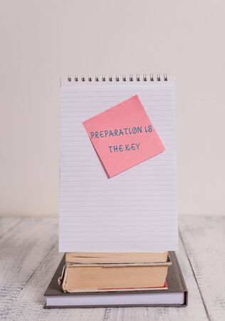Writing note showing Preparation Is The Key. Business concept for it reduces errors and shortens the activities Stacked books spiral note book sticky lying vintage retro wooden table