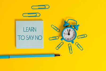 Word writing text Learn To Say No. Business photo showcasing decline or refuse few things before you destroy yourself Metal alarm clock wake up clips ballpoint notepad colored background
