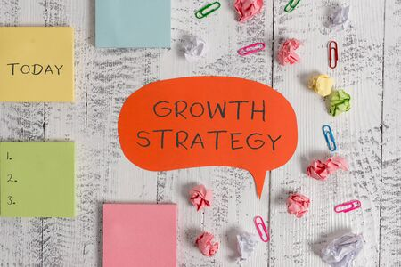 Word writing text Growth Strategy. Business photo showcasing Strategy aimed at winning larger market share in shortterm Blank speech bubble paper balls clips sticky notes old wooden background