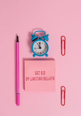 Conceptual hand writing showing Get Rid Of Limiting Beliefs. Concept meaning remove negative beliefs and think positively Metal alarm clock blank notepad marker clips colored background