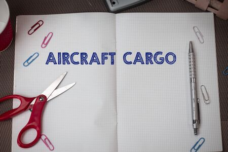 Conceptual hand writing showing Aircraft Cargo. Concept meaning Freight Carrier Airmail Transport goods through airplane Scissors and equipments math book above textured backdrop