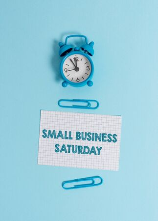 Handwriting text writing Small Business Saturday. Conceptual photo American shopping holiday held during the Saturday Alarm clock wakeup squared blank paper sheet clips colored background