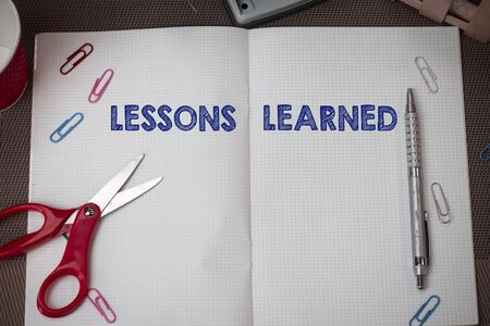 Conceptual hand writing showing Lessons Learned. Concept meaning information reflects positive and negative experiences Scissors and equipments math book above textured backdrop