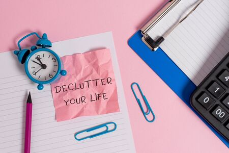 Conceptual hand writing showing Declutter Your Life. Concept meaning To eliminate extraneous things or information in life Paper sheet clipboard pencil calculator clock colored background Banque d'images