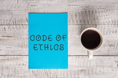 Conceptual hand writing showing Code Of Ethics. Concept meaning basic guide for professional conduct and imposes duties Stationary placed next to a coffee cup above wooden table